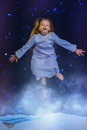 A portrait of a young pretty emotional girl flying in the sky in dream. Dreams, pajamas.