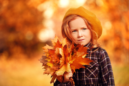 Autumn. Little girl walks through a beautiful autumn park and collects leaves fallen from trees. Retro style. Children's fashion. Stock Photo