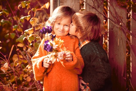 Cute little boy presents a rose to his little lady in a beautiful autumn park. Childrens fashion. Retro style.