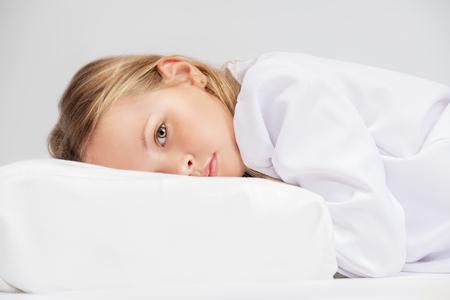 Un retrato de una niña bonita en la cama. Relájate, pijama.