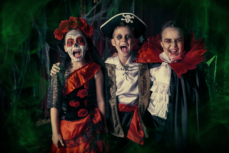 Scared children celebrate Halloween on a party with old castle decorations. Halloween. Stock Photo