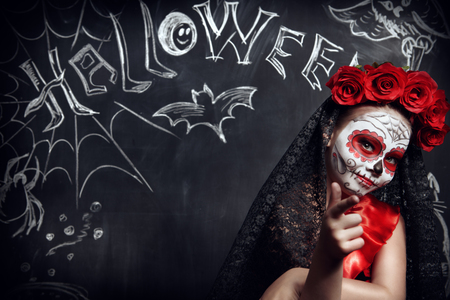 Portrait of a child girl in a costume of Calavera Catrina posing by a chalkboard with Halloween decoration. Little girl with sugar skull makeup. Halloween party. Dia de los muertos. Day of The Dead. 스톡 콘텐츠