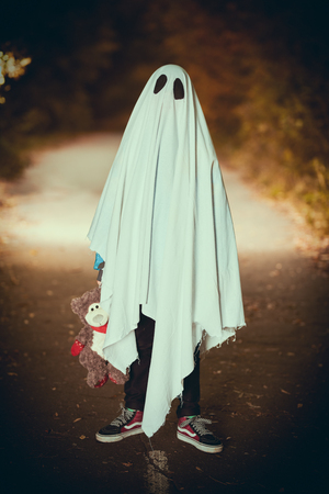 Lonely ghost of a child under a white sheet stands with his teddy bear in a dark forest. Halloween. Stock fotó
