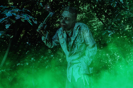 Terrible bloody zombie with an ax in his hands in the night forest. Halloween. Thriller. 写真素材