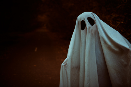 A lonely ghost of a child under a white sheet stands on a deserted road in the forest. Halloween. Copy space.