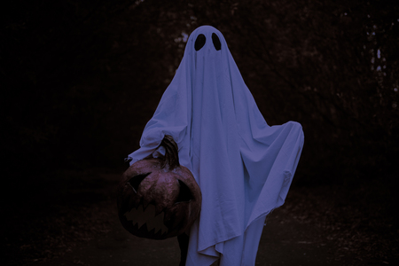 A ghost of a child under a white sheet stands in a shadow forest with pumpkin lantern. Halloween concept.
