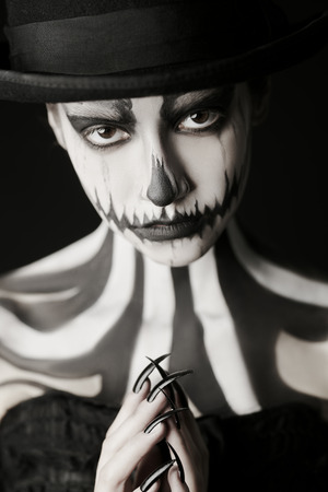 Close-up portrait of an elegant young woman in a male top-hat with pumpkin skull make-up over black background. Pumpkin queen. Costumes and makeup for Halloween.