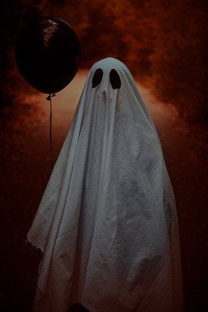 A lonely ghost of a child under a white sheet stands with a black balloon on a deserted road in the forest. Halloween.