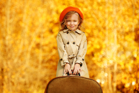 Pretty little girl stands with her old fashioned suitcase in the autumn park. Retro style. Children's fashion.