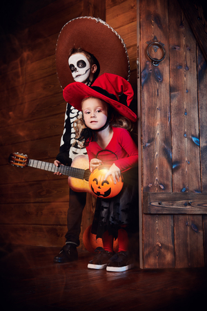 Happy children in witch and skeleton costumes celebrate halloween. Trick or treat. Halloween. Dia de los muertos. Day of The Dead.