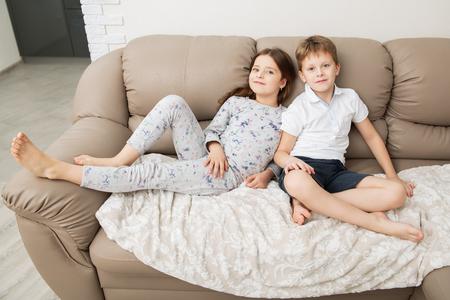 Ragazzo e ragazza carini sono seduti sul divano. Colpo domestico di moda. Infanzia. Moda per bambini. Archivio Fotografico