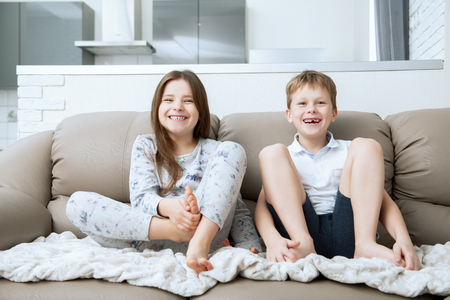 Cute boy and girl are  sitting on the couch.  Fashion home shot. Childhood. Kid's fashion. 스톡 콘텐츠