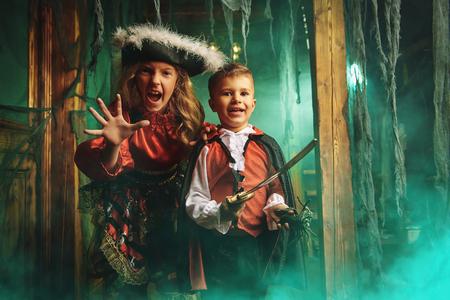Happy children in carnival costumes celebrate halloween in the old castle. Halloween. 版權商用圖片