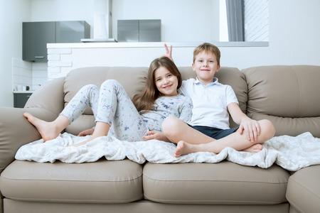 Netter Junge und Mädchen sitzen auf der Couch. Mode nach Hause geschossen. Kindheit. Kindermode. Standard-Bild