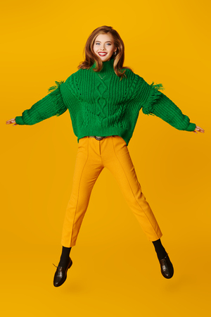 Fashion shot. Full length portrait of a beautiful happy girl in bright clothes jumping for joy over yellow background. Copy space.