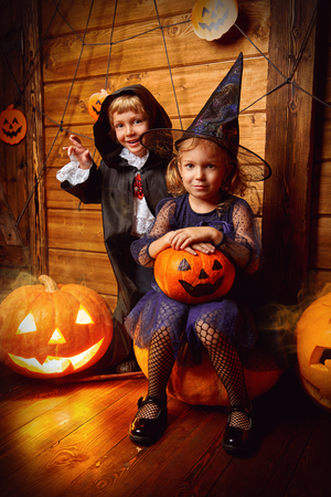 Happy children in witch and vampire costumes celebrate halloween. Trick or treating. Halloween. Banco de Imagens