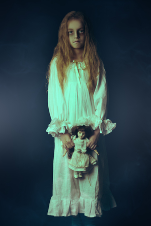 Scary little girl ghost in a white nightgown holds her doll. Black background. Halloween. Stock fotó