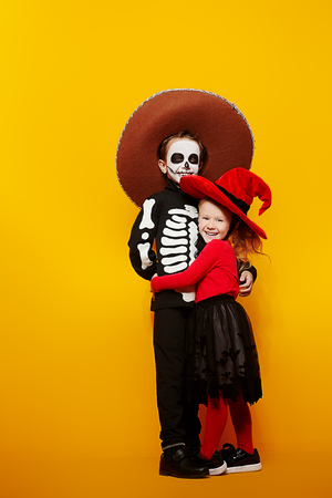 Halloween. Portrait of two cute kids in witch and skeleton costumes over yellow background. Dia de los muertos. Day of The Dead. Copy space.