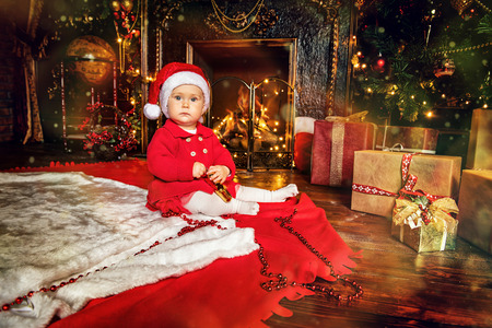 A little newborn baby is on the floor in the interior decorated for Christmas. Merry Christmas, Happy New Year. Miracle time.