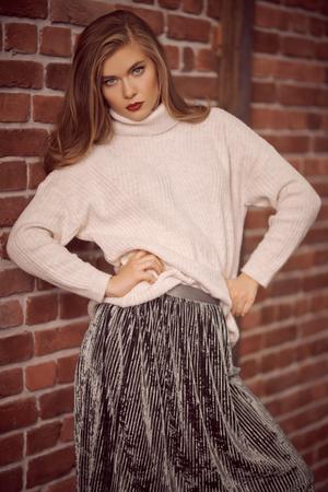 Fashion shot. Modern female model posing at studio over brick wall background.