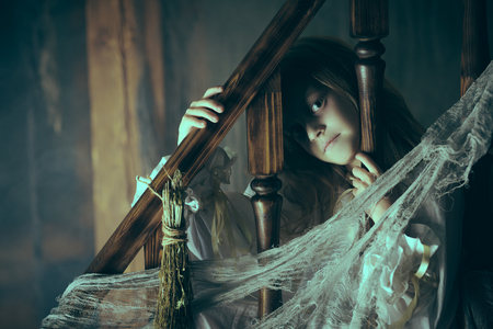 Little girl ghost in a nightgown wanders through the old house at night. Halloween. Stock fotó