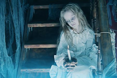 Halloween. Ein Geistermädchen im Nachthemd wandert nachts durch das alte Haus. Standard-Bild