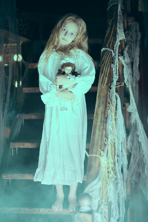 Little girl ghost in a nightgown wanders through the old house with a doll in his hands at night. Halloween. Stock fotó