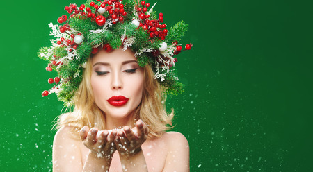 Charming Christmas young woman blows snow from palms. Christmas magic atmosphere, lights and snowfall. festive pine headdress decorated with Christmas balls, berries and snowflakes.  Copy space. Stok Fotoğraf
