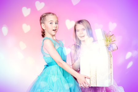 Two pretty little girls dressed in beautiful festive dresses open a gift box. Kids fashion concept. Stock Photo