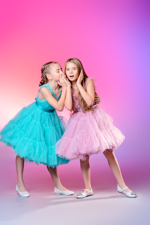 Dos bonitas niñas vestidas con hermosos vestidos de fiesta. Concepto de moda infantil.