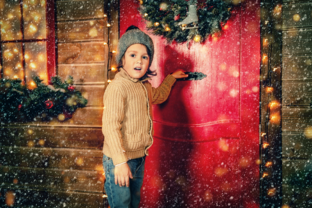 A little boy is standing near the house decorated for Christmas. Miracle time. Merry Christmas and Happy New Year. Stock Photo