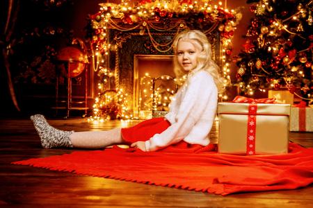 Ein schönes Mädchen freut sich zu Hause über die Geschenkbox, die sie bekommen hat. Fröhliche Weihnachten und frohes Neues. Wunderzeit. Standard-Bild