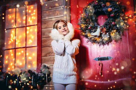 Pretty child girl is standing near her house decorated for Christmas in fur earmuffs and mittens. Warm winter accessories. Merry Christmas and Happy New Year.