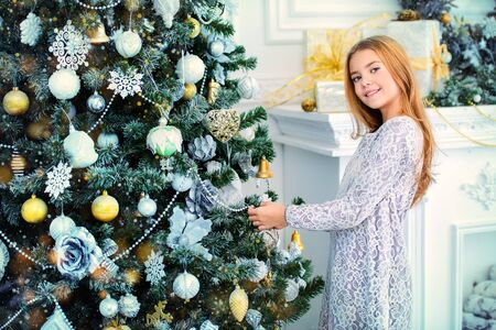 Happy child girl in a beautiful white dress decorates the Christmas tree. Merry Christmas and Happy New Year.