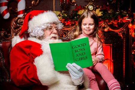 A happy young girl Santa Claus are sitting and reading book at home. Merry Christmas and Happy New Year. Miracle time.