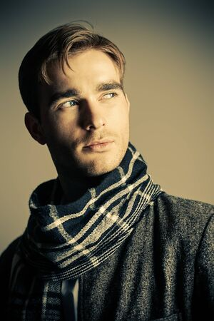 Male beauty, fashion. Portrait of a handsome man wearing coat and scarf. Seasonal clothes collection.