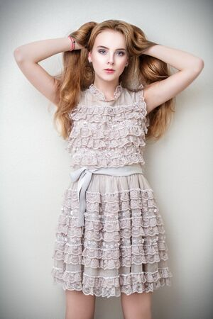 Portrait of a cute girl in standing lace dress and leaning on the wall in the room. Beauty, fashion. Banco de Imagens
