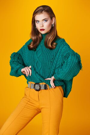 Fashion shot. Portrait of a beautiful modern girl in bright clothes over yellow background. Copy space. 版權商用圖片