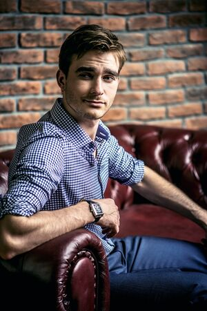 Handsome young man demonstrating his wrist watch. Stock Photo