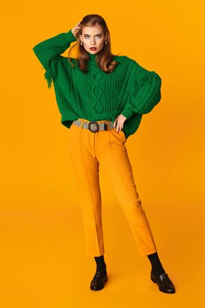 Fashion shot. Full length portrait of a beautiful modern girl in bright clothes over yellow background. Copy space.