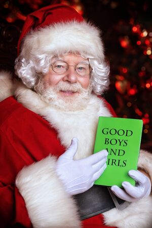 A portrait of Santa Claus sitting at his home with book about good boys and girls. Miracle time. Christmas, New Year.