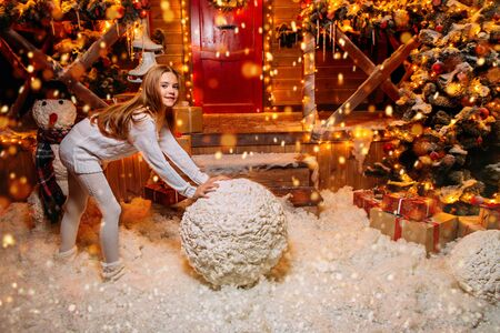 Pretty child girl sculpts a snowman near her house decorated for Christmas. Merry Christmas and Happy New Year.