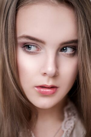 A close up portrait of a cute girl teenager with long light brown hair.