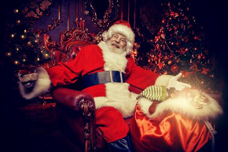 A portrait of Santa Claus sitting at his home decorated for Christmas near the bag with gifts and making a garland. Miracle time. Christmas, New Year. Imagens