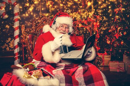 A portrait of Santa Claus is sitting in the headset with a laptop at his home. Miracle time. Christmas, New Year.