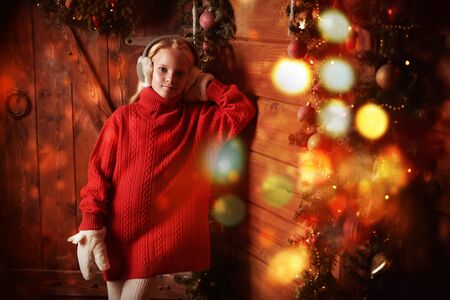 Christmas and New Year concept. Happy cute girl child in winter clothes stands in a wooden house decorated with Christmas spruce garlands and toys. The atmosphere of celebration and magic, lights and sparkle is around.