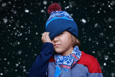 Portrait of a cute emotional boy child in winter clothes under the snow.