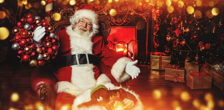 A portrait of Santa Claus sitting and holding a wreath of balls near the bag with gifts at his home decorated for Christmas near the bag with gifts. Miracle time. Christmas, New Year.