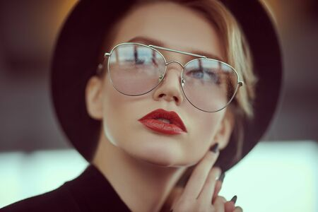 Close-up portrait of a fashionable young woman in modern glasses and hat in interiors. Stock Photo