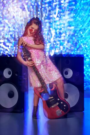 Christmas and New Year kid's party. Cool little girl sings and dances with an electric guitar next to the speakers. Disco and lights. Standard-Bild - 133892342